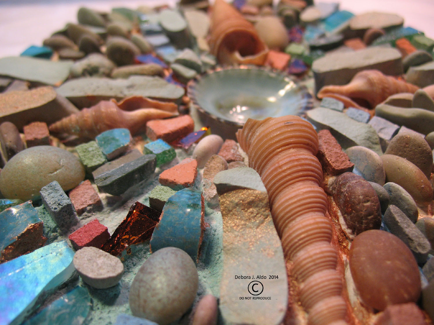 Pebbles, Rusted discarded hardware, shells, colored thinset.
